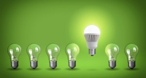 Row of light bulbs. Idea concept on green background.